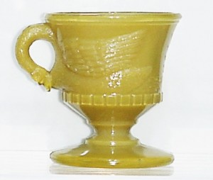 """Swimming Swan"" mug in odd opaque mustard glass, attributed to Atterbury."