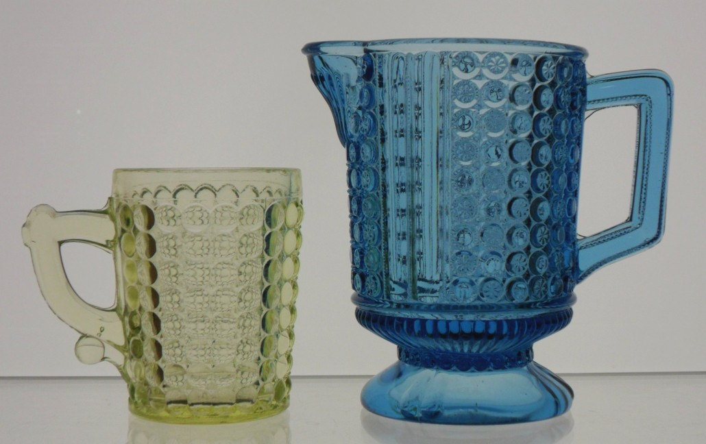 "EAPG: Vaseline Glass ""Thousand Eye"" pattern mug (Adams & Company or Richards & Hartley, Pittsburgh); blue ""Three Panel"" cream pitcher (Richards & Hartley)."