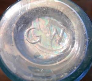 Base of cylindrical castor oil or medicine bottle (left in group photo, above)