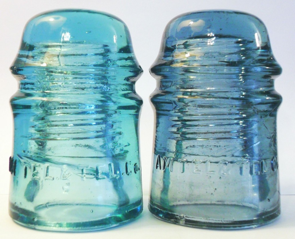 "Two ""AM TEL & TEL CO"" insulators made by Brookfield Glass Company for AT&T CO in the 1900s-1910s. The piece on left is the natural as-found aqua color. The example on RIGHT has been irradiated which has produced an odd ""cornflower"" or ""dingy sapphire"" blue shade."