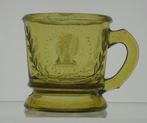 Ceres or Cameo (original pattern name Medallion) mug in yellow amber. This is a different mold than the example in blackglass, below.