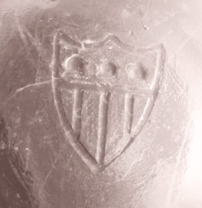 Shield logo on the base of an antique glass jelly jar or tumbler