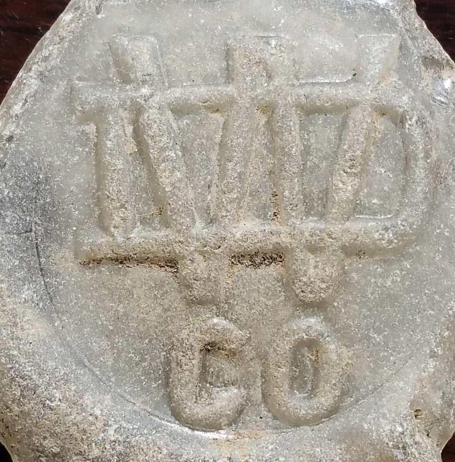 WDCO monogram, as it appears on beach glass (bottle base). Photo courtesy of Natalie Radosevic.