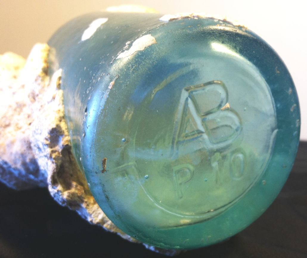 AB / P 10 bottle (encrusted with coral) as found off coast of Maui. (Photo courtesy of Betsy Sears).